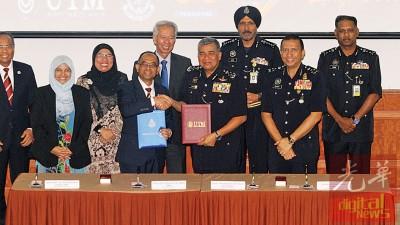 卡立(前排右2)与马来西亚工艺大学代表签署备忘录后,握手示意。