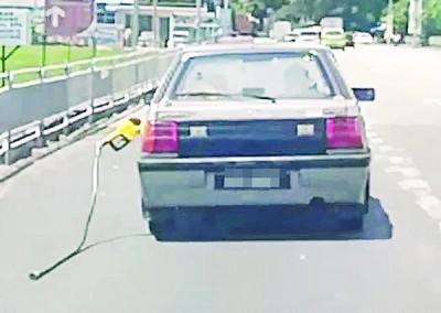 车主在扯断油管后还不自知,油箱插着油枪,拖着长长的油管在路上行驶。(档案照)