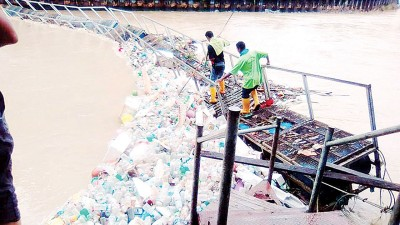 双溪槟榔在水灾后有许多垃圾漂浮在河流中央,多数是塑料水瓶,而槟岛市政厅清洁工友在努力清理垃圾。