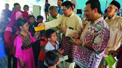 (右起)阿兹曼、王敬文、曼梳派发青包给在场的毛孩子。