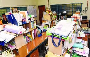 """教师行政室空间有限,11位教员挤在狭隘的空间,文件的无处可放造成必须叠高置放,形同老师与老师之间的""""柏林围墙""""。"""