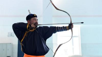 7月14日,乌恩奇在内蒙古自治区陈巴尔虎旗第二中学射箭馆向外地游客展示蒙古族传统射箭技艺。