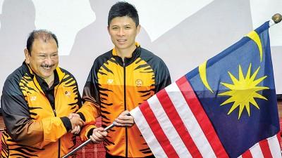 东姑英南(左)授旗给青年共运会团长黄综翰。