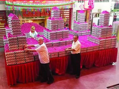孙幸福及村长洪铷鸿协助堆砌蛋塔。