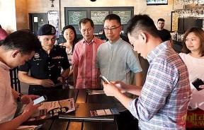 江靖程提供手机联络号码给商家及顾客们,以便能够在第一时间提供讯息共同打击罪案。陈书北(右3)及陈珊珊(右1)协助解说。