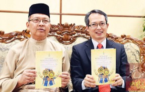 法力占(左)及刘子健出示2017年度槟州元首华诞受封人士名册。