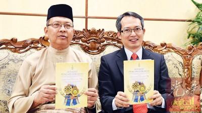 法力占(左)和刘子健著2017东槟州元首华诞受封人士名单。