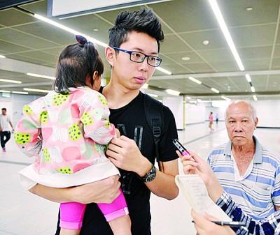 欧国健(左)与父亲带着女儿乘搭捷运,熟悉环境。