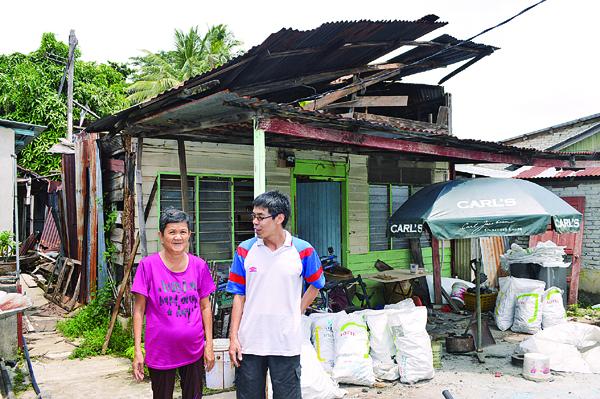 邱春威(右)向徐玉凤了解破烂板屋的情况。