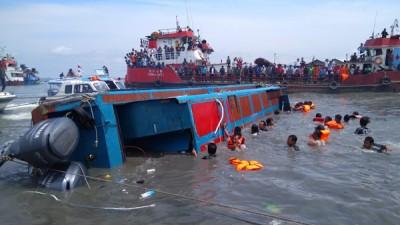 搜救人员在快艇翻覆海域搜寻失踪乘客。(法新社照片)