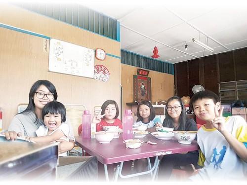 两位义工邓懿慧及黄淑玲与3位学生一起开心吃饭。