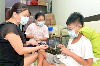 庐健平(右)生病末期肾衰竭,换肾前每天要在家洗肾长达14时。(档案照)