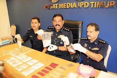安华奥玛(左二)与查案官向媒体展示起获的毒品。