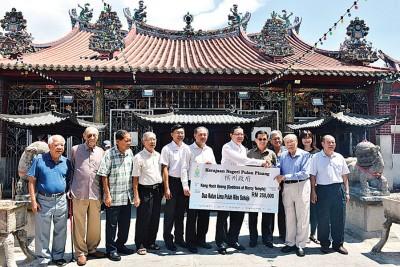 槟首长林冠英(左7)移交25万令吉拨款模拟支票予信理会主席邱吉寿。