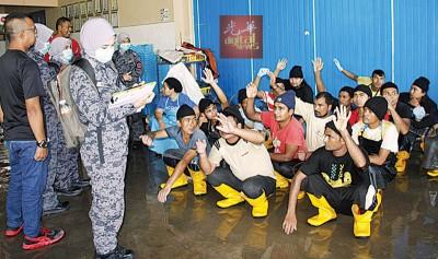 吉州移民局执法人员突击位于槟榔再也的一间宰鸡厂。