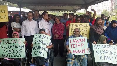 大批村民高举海报要求暂时不要收回甘榜土地,当中以老弱妇孺为多,也有一些长者坐着轮椅出动护村。站着左4为拉昔、再里尔(左3)及沈志强(左2)。