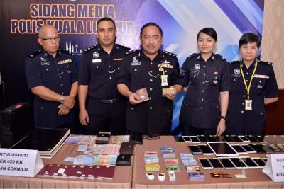 鲁菲(中)与立功警官在记者会出示电话诈骗集团成员使用的工具,右为吉隆坡警察商业罪案调查组高级查案官陈宝祝副警监。