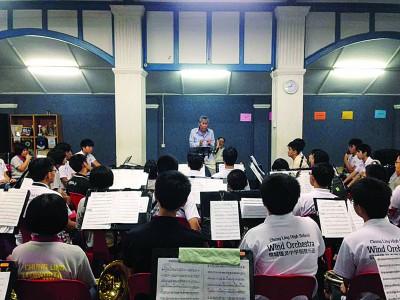 谈名光为槟城锺灵中学钢管乐团担任指挥。