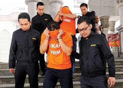 2名嫌犯周六由获得延扣令的反贪会人员押离法庭时,纷纷以橙色扣留犯服掩脸。