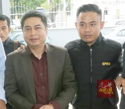 被告沙比里(左)让反贪会官员押往法庭面控。