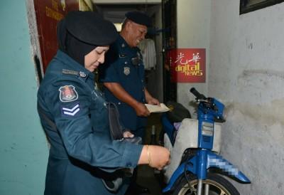 吉隆坡市政局执法人员对犯罪在组屋一楼单位外停泊的摩托车发出传票。