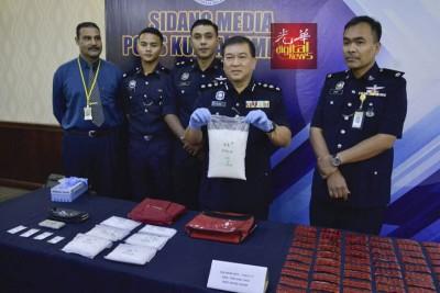 颜明江(右2)向记者出示起获的毒品。