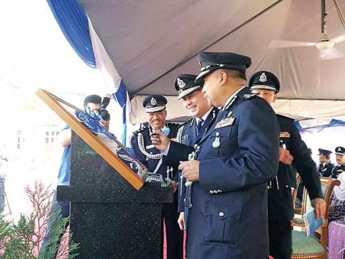 莫达(右)为实里拉龙警局主持开幕典礼提笔留名。面向镜头左起是莫哈末拉汉及旺阿末。