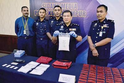 颜明江(右2)向记者出示起犾的毒品。
