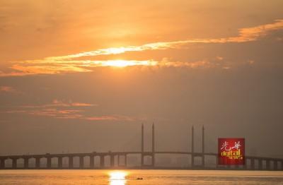 摄影爱好者从班台惹雅码头拍摄日出时,拍到海豚嬉戏。