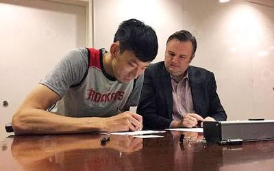 周琦(左)完成签署合同后正式登陆NBA,身旁为休斯顿火箭队总经理达雷尔莫雷。