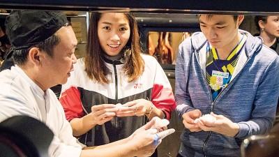 泰国女单首号种子拉查诺(面临)以及王子维(右)每当赛前抽空参与大会活动,让餐厅学习制作中式点心。