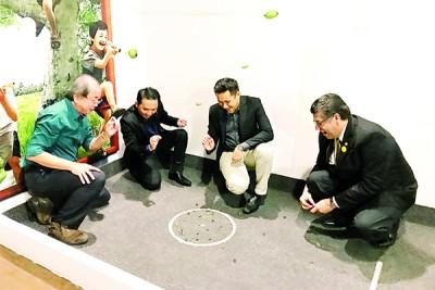 左起骆锦地、胡国强、刘荣鸿及菲力童心未泯玩玻璃弹珠的游戏。