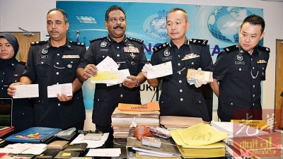泰维根(中)及沙克里(右2)展示警方行动中起获的账簿及放贷资料等。