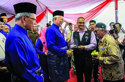 纳吉(左2)在与领袖会面活动上,与患病的出席者交流。左为慕斯达化。