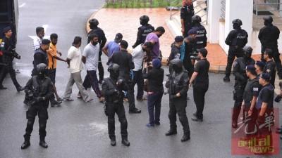 """159名全副武装的特警押送33名""""24党""""党徒到法庭面控。"""