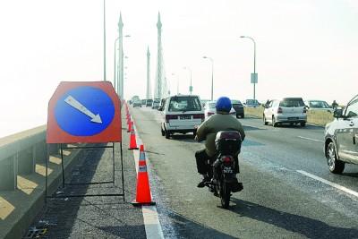 迫车道遭封路,骑士与轿车共用一个车道。