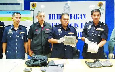 莫哈末拉扎里(左3起)及宋萨展示警方搜获的大麻及海洛英。
