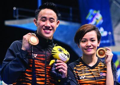 黄兹梁和张俊虹展示获得的吉隆坡东运会男子10米台和女子1米板金牌。