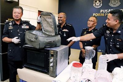 州总警长蔡义来(左)于媒体展示起获的制毒工具。