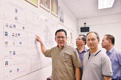梁国伟(左)向媒体展示班丹区会领导层结构图,力证该涉案人并没在领导层榜单中。