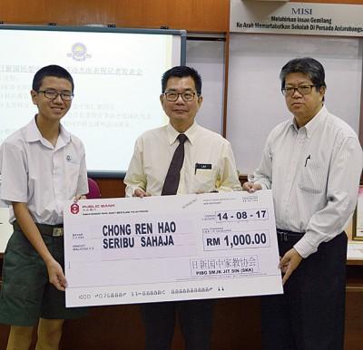 郑克林(右)移交模拟支票予张仁豪(右),以奖励他在3项国际数学比赛夺得金奖,林钿洝(中)见证。