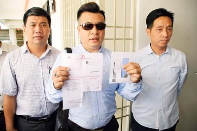 蔡永霖(中)出示门牌税收据和装有钥匙的信封,在胡栋强(右起)和民政党峇都兰樟协调员吴汉仁陪同下召开记者会。