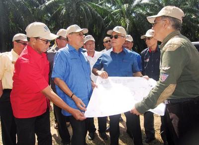阿末峇沙(左2)在赛车场地段聆听工作进展汇报。