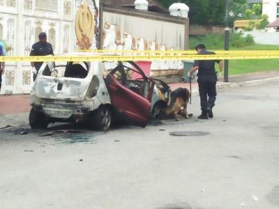失火的轿车已成废铁,警方出动警犬协助调查。