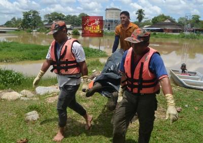 自愿消防队员协助将死者遗体捞起。