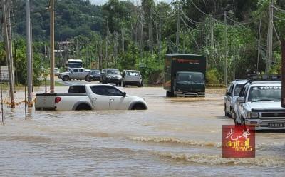 一辆四驱车因无法横渡水势高涨的道路而抛锚。