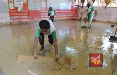 达瑙国小学生在水灾后,纷纷回校清理被泥水蹂躏的校园与课室。