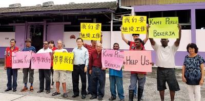 廖泰义与都拜宰猪场员工持海报,促新管理层重新聘请他们。