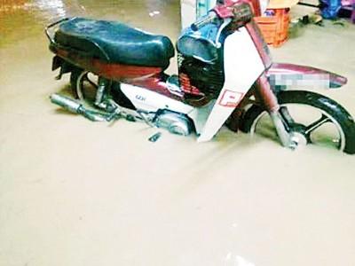 成杰村镇发生内涝,一辆来不及移走的摩托车浸泡在水中。
