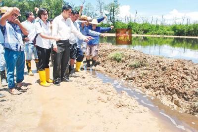孙意志(右4)在众村民与业者陪同下巡视污染的排水沟。